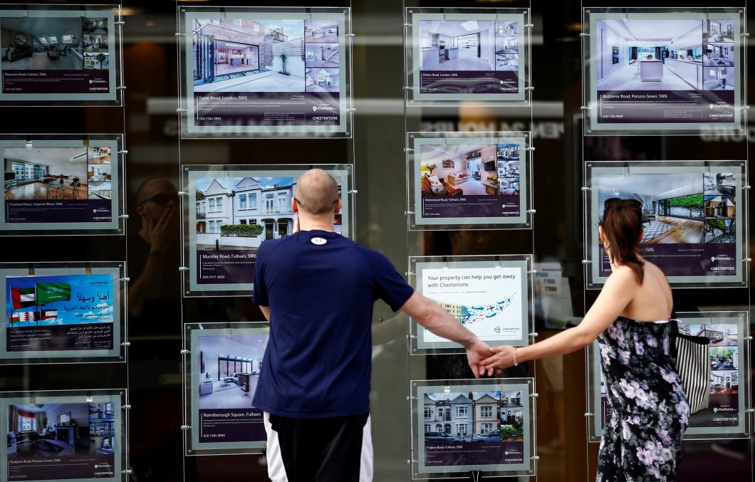 A couple view properties for sale in an estate agents window in London